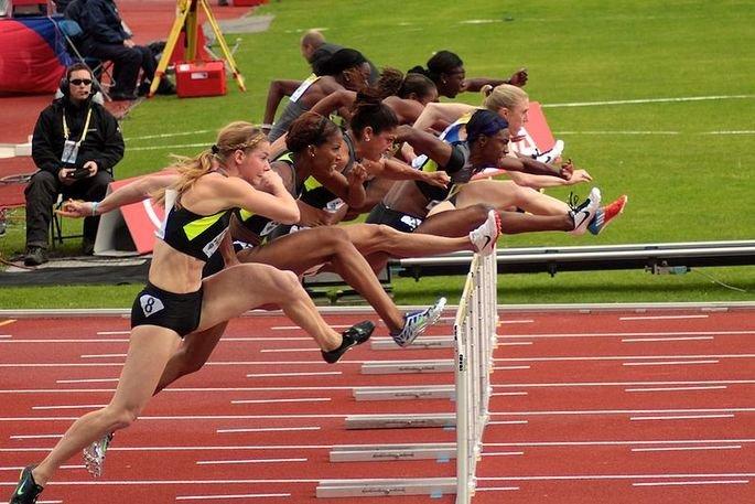Atletas saltando obstáculo em prova de 100 m com barreiras
