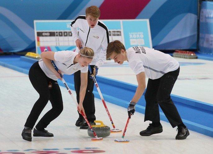 Atletas de curling competindo