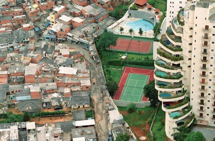 Favela e prédio de luxo separados por um muro