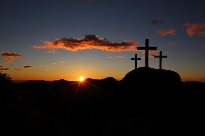 três cruzes no alto de uma montanha ao pôr do sol