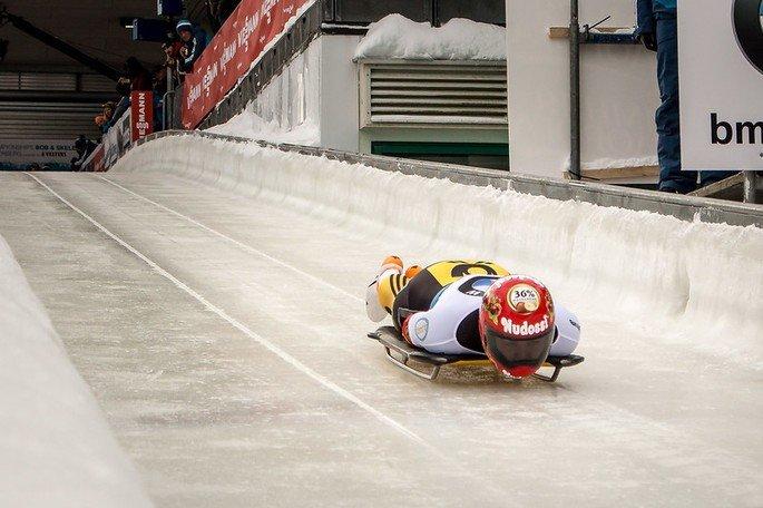 Atleta descendo deitado sobre um trenó